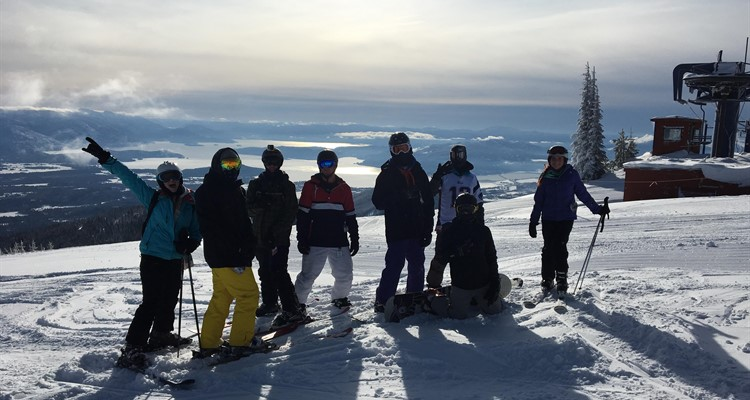 Post Falls students involved in ski and snowboard club pose atop Schweitzer Mt. on a bluebird day.